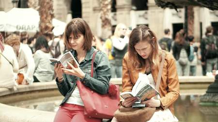 BARCELONA, SPAIN - APRIL, 16, 2017. Two young women reading city tourist guide books near the fountain