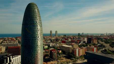 BARCELONA, SPAIN - APRIL, 15, 2017. Torre Agbar skyscraper, city and seafront aerial view on a sunny day Editorial