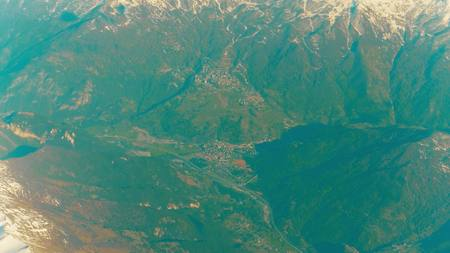 ridgeline: The Alps mountains and alpine town in a valley. Aerial shot Stock Photo