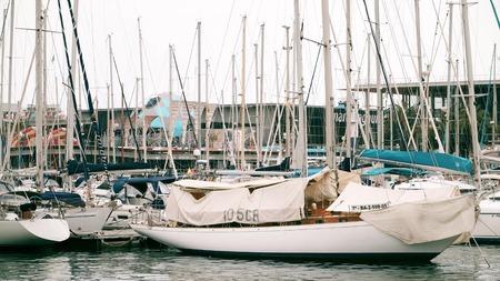 navy pier: BARCELONA, SPAIN - APRIL, 15, 2017. Moored sailing boats at the marina piers Editorial