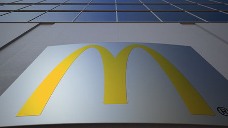 Outdoor signage board with McDonalds logo. Modern office building. Editorial 3D
