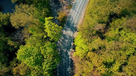 street shot: Aerial shot of a forest car road bend, top down view Stock Photo