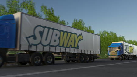 famous industries: Freight semi trucks with Subway logo driving along forest road. Editorial 3D rendering