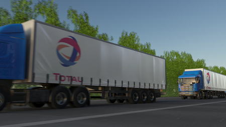 Freight semi trucks with Total S.A. logo driving along forest road. Editorial 3D rendering