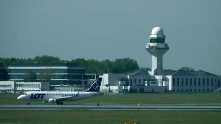airfield: WARSAW, POLAND - MAY, 18, 2017. LOT Polish airlines airplane takeoff and Chopin airport control tower beyond runway heat haze. Telephoto lens shot