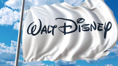 Waving flag with Walt Disney logo against sky and clouds. Editorial 3D rendering