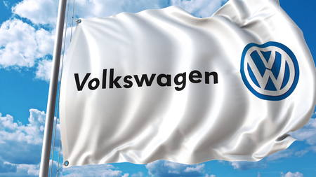 Waving flag with Volkswagen logo against sky and clouds. Editorial 3D rendering Editorial