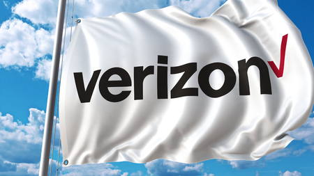 Waving flag with Verizon logo against sky and clouds. Editorial 3D rendering