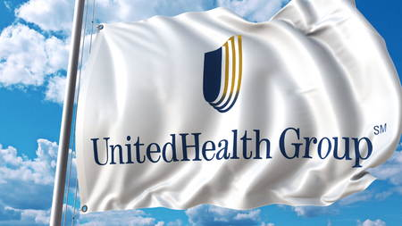 Waving flag with Unitedhealth Group logo against sky and clouds. Editorial 3D rendering