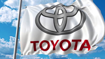 Waving flag with Toyota logo against sky and clouds. Editorial 3D rendering Editorial