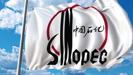 Waving flag with Sinopec logo against sky and clouds. Editorial 3D rendering