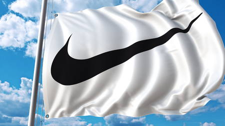 Waving flag with Nike logo against sky and clouds. Editorial 3D rendering Editorial