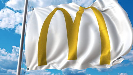 Waving flag with McDonalds logo against sky and clouds. Editorial 3D rendering