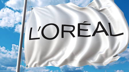 Waving flag with Loreal logo against sky and clouds. Editorial 3D rendering