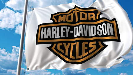 Waving flag with Harley-Davidson logo against sky and clouds. Editorial 3D rendering