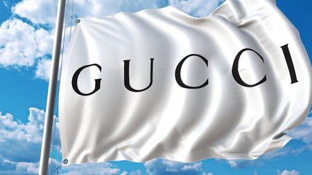 Waving flag with Gucci logo against sky and clouds. Editorial 3D rendering Editorial