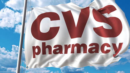 Waving flag with Cvs Pharmacy logo against sky and clouds. Editorial 3D rendering