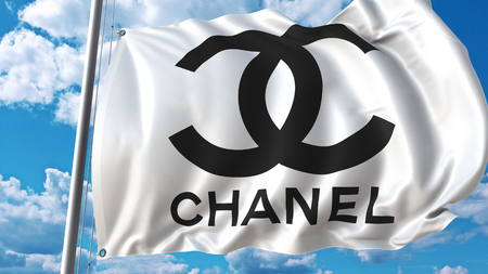 chanel: Waving flag with Chanel logo against sky and clouds. Editorial 3D rendering