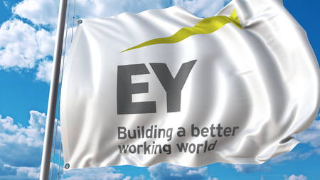 Waving flag with EY logo against sky and clouds. Editorial 3D rendering