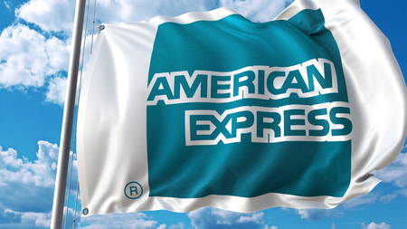 Waving flag with American-Express logo against sky and clouds. Editorial 3D rendering