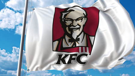 Waving flag with KFC logo against sky and clouds. Editorial 3D rendering