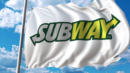Waving flag with Subway logo against sky and clouds. Editorial 3D rendering