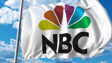 Waving flag with NBC logo against sky and clouds. Editorial 3D rendering