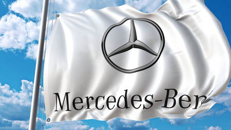 Waving flag with Mercedes-Benz logo against sky and clouds. Editorial 3D rendering