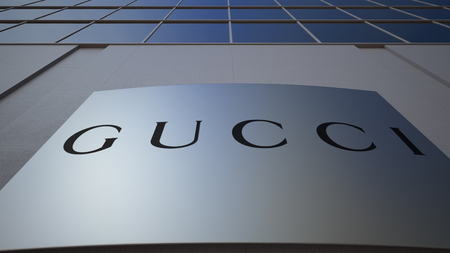 Outdoor signage board with Gucci logo. Modern office building. Editorial 3D rendering