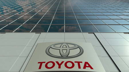Signage board with Toyota logo. Modern office building facade. Editorial 3D rendering