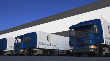 commercial medicine: Freight semi trucks with UnitedHealth Group logo loading or unloading at warehouse dock. Editorial 3D rendering