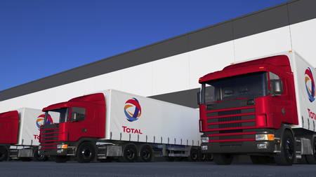 Freight semi trucks with Total S.A. logo loading or unloading at warehouse dock. Editorial 3D rendering