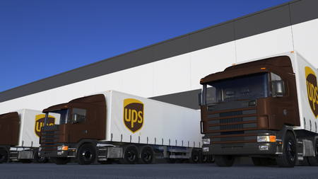 Freight semi trucks with United Parcel Service UPS logo loading or unloading at warehouse dock. Editorial 3D rendering Editorial