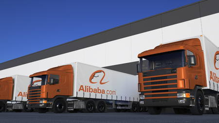 Freight semi trucks with Alibaba.com logo loading or unloading at warehouse dock. Editorial 3D rendering