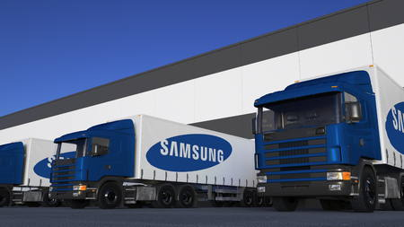 logo samsung: Freight semi trucks with Samsung logo loading or unloading at warehouse dock. Editorial 3D rendering