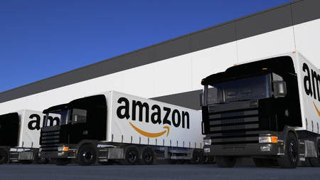 Freight semi trucks with Amazon.com logo loading or unloading at warehouse dock. Editorial 3D rendering