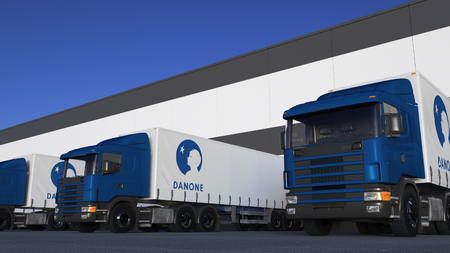 Freight semi trucks with Danone logo loading or unloading at warehouse dock. Editorial 3D rendering