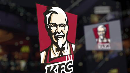 Kentucky Fried Chicken KFC logo on the glass against blurred business center. Editorial 3D rendering