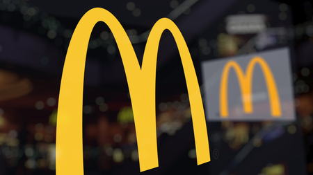 McDonalds logo on the glass against blurred business center. Editorial 3D rendering