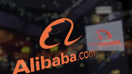Alibaba.com logo on the glass against blurred business center. Editorial 3D rendering