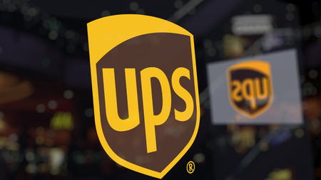 United Parcel Service UPS logo on the glass against blurred business center. Editorial 3D rendering Editorial