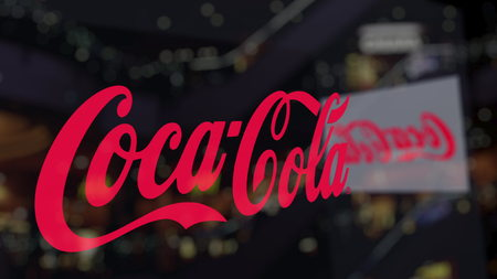 Coca-Cola logo on the glass against blurred business center. Editorial 3D rendering