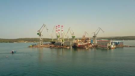 shipbuilding: PULA, CROATIA - AUGUST 4, 2017. Aerial view of the Uljanik shipyard cranes and unfinished ship