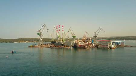 PULA, CROATIA - AUGUST 4, 2017. Aerial view of the Uljanik shipyard cranes and unfinished ship
