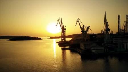 PULA, CROATIA - AUGUST 5, 2017. Aerial view of the Uljanik shipyard cranes silhouettes at sunset