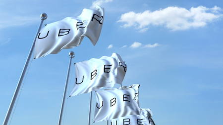 Waving flags with Uber logo against sky, editorial 3D rendering