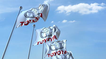 Waving flags with Toyota logo against sky, editorial 3D rendering Editorial