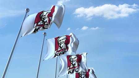 Waving flags with KFC logo against sky, editorial 3D rendering