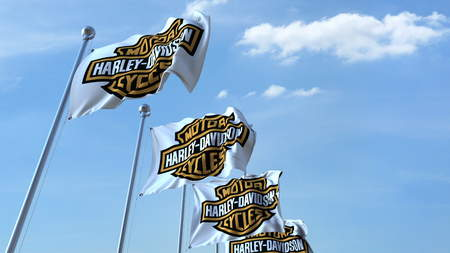 Waving flags with Harley-Davidson logo against sky, editorial 3D rendering