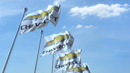 Waving flags with Chevrolet logo against sky, editorial 3D rendering